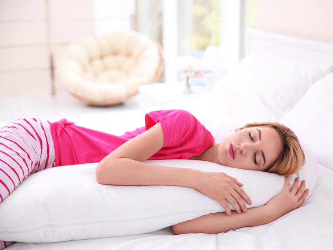 抱き枕を抱いて寝る女性