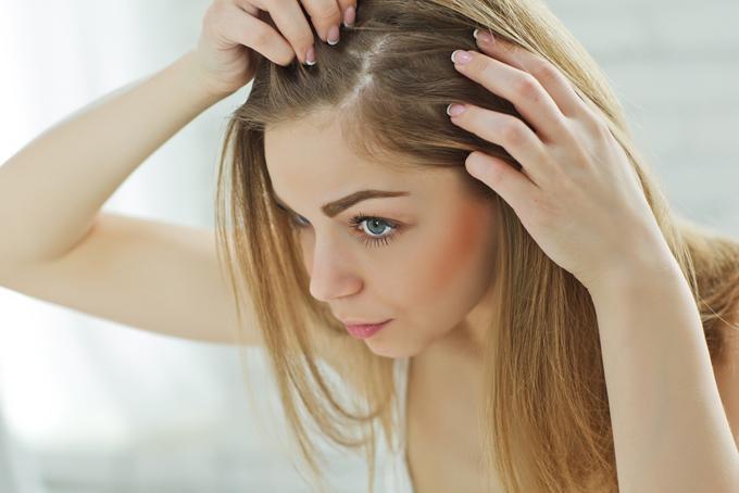 髪の毛の分け目を気にしている女性の画像