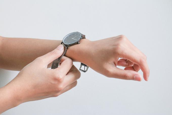 時計を腕にはめる女性