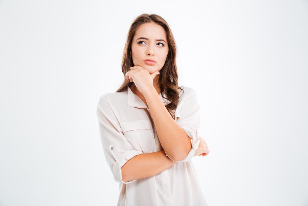 腕を組んで疑問の表情を浮かべる女性