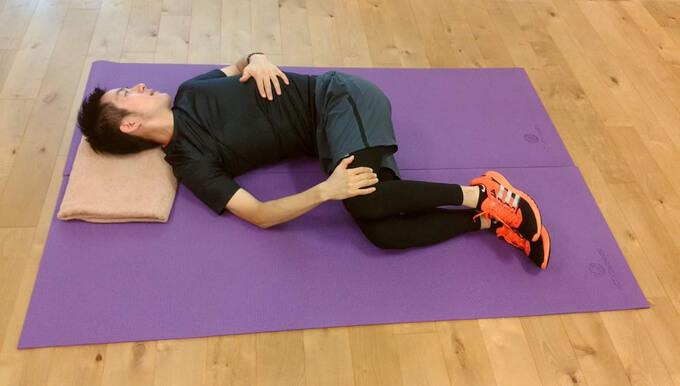伊藤さんが横向きに寝て、ろっ骨を横に開くように胸を開いていく画像