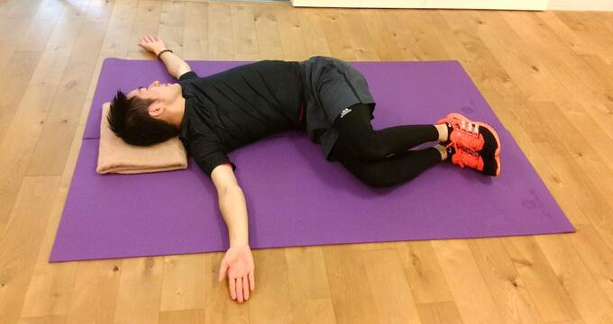 伊藤さんが横向きに寝て、上の腕を後ろへ開いていき、胸を広げている画像