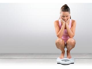 体重計に乗って悩む女性