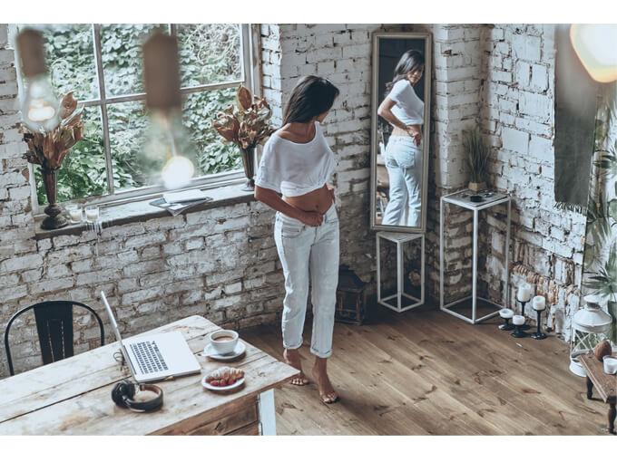 全身を鏡に映している女性