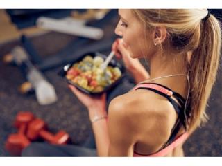 トレーニングの前に食事をする女性