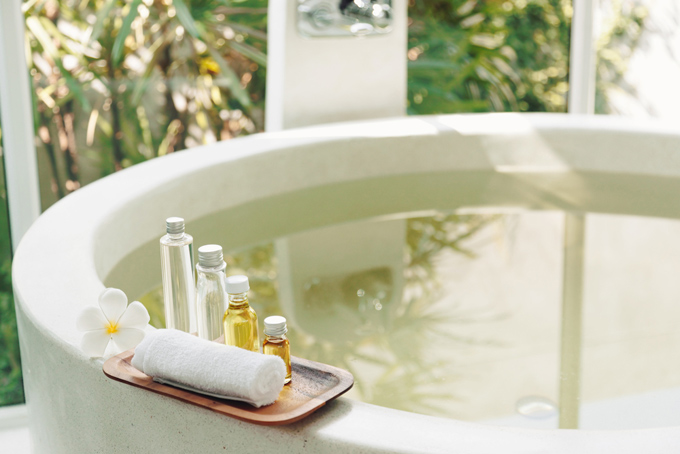 白くて丸いお風呂の淵にアメニティが置いてあるイメージ画像