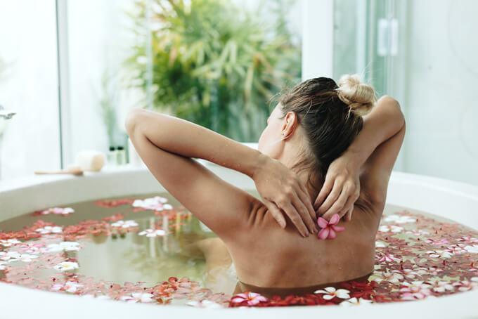 女性が手を背中に回してストレッチしている入浴中の女性の後ろ姿