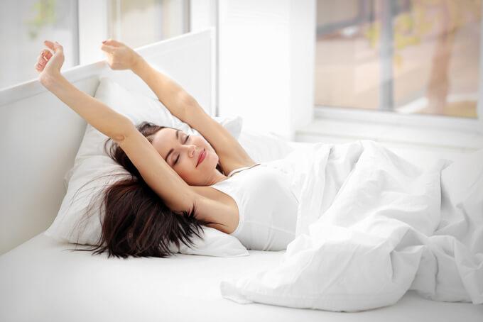ベッドで伸びをしている女性の画像