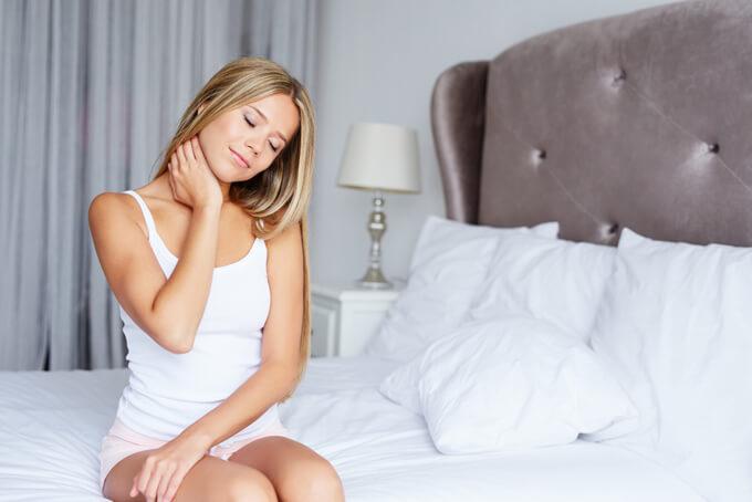 ベットに座って肩を触っている女性の画像