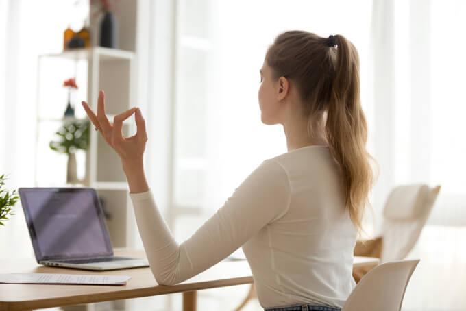 PCの前で瞑想をしている女性の後ろ姿