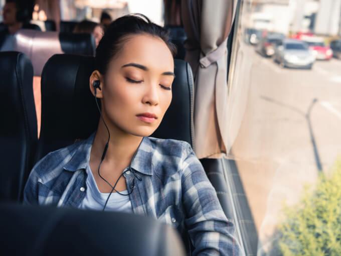 電車の座席で居眠りしている女性の画像