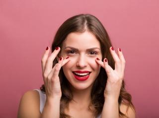 目の周りに手を当てている女性の画像