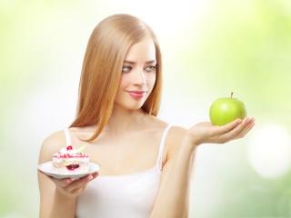 片手にケーキと片手にりんごを持つ女性