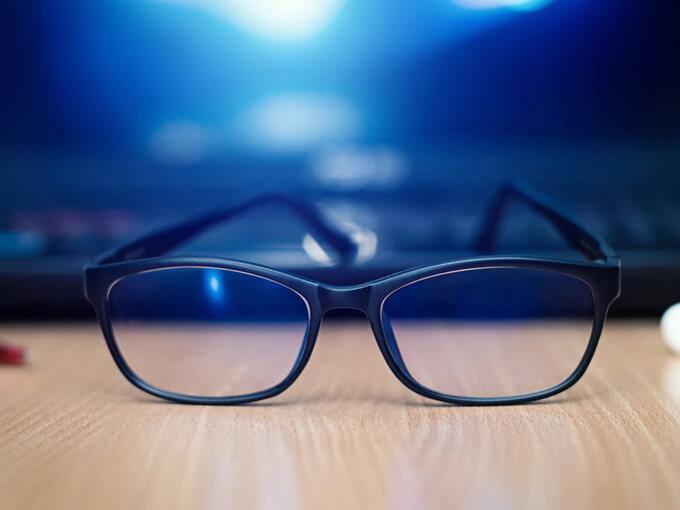 パソコンの前に眼鏡が置いてあるイメージ画像