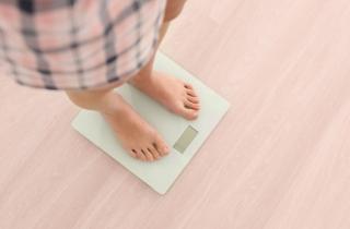 体重計にのる女性の画像