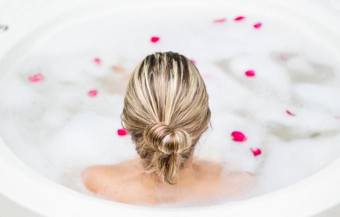 お風呂に入って髪の毛をアップしている女性の後ろ姿画像
