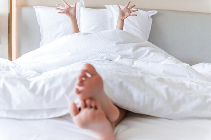 ベッドで手をあげて指を開いている女性の画像