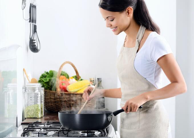 女性が料理をしている画像