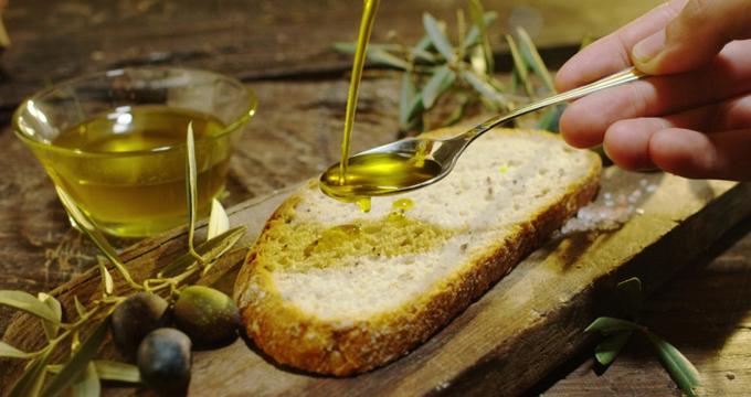 パンにオリーブオイルをかけている