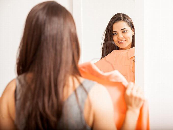 服をあわせて鏡を見る女性