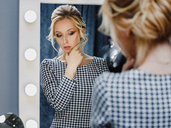 鏡にうつる自分の姿を見て浮かない表情の女性