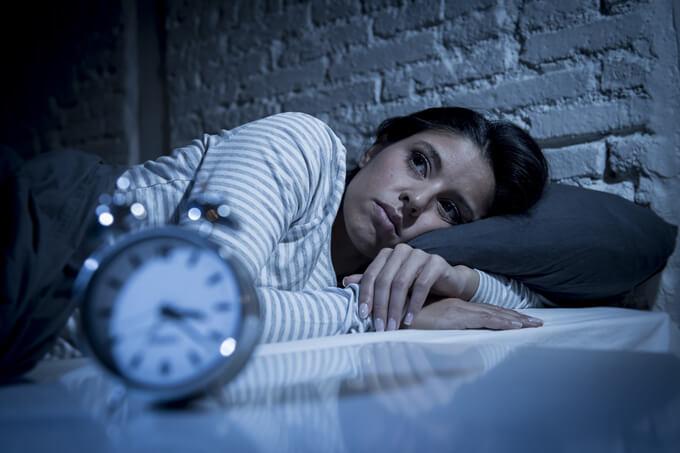 ベッドの上で横になっている女性と目覚まし時計の画像