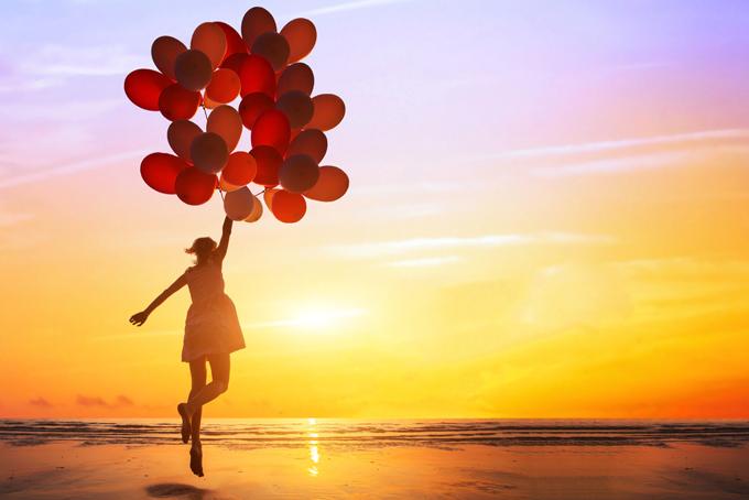 風船に捕まって空を飛んでいる女性のイメージ画像