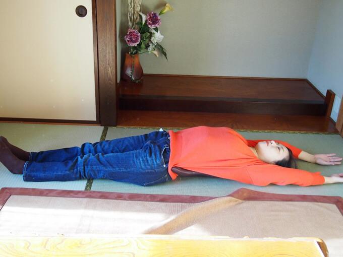 腰の下にグッドコアを置いて体をのばす藤井さん