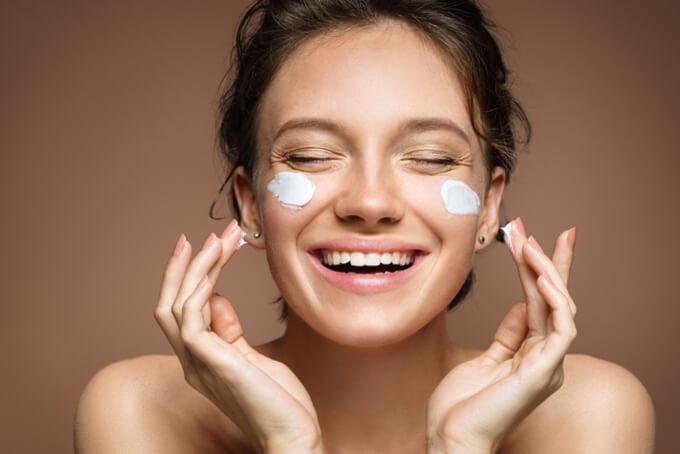 顔にクリームを塗って笑顔の女性