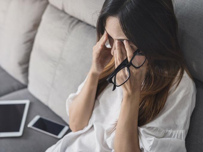 眼鏡を外して眼を押さえている女性の画像