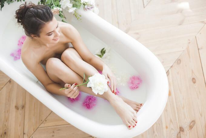 花が浮かぶお風呂に入ってリラックスしている女性の画像
