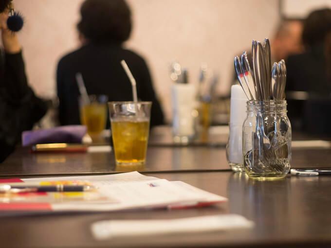 テーブルの上にノートとペン、飲み物が置いてある画像