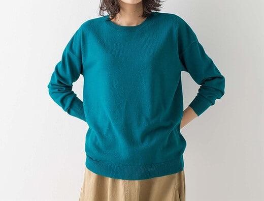 エメラルドグリーンのニットを着た女性