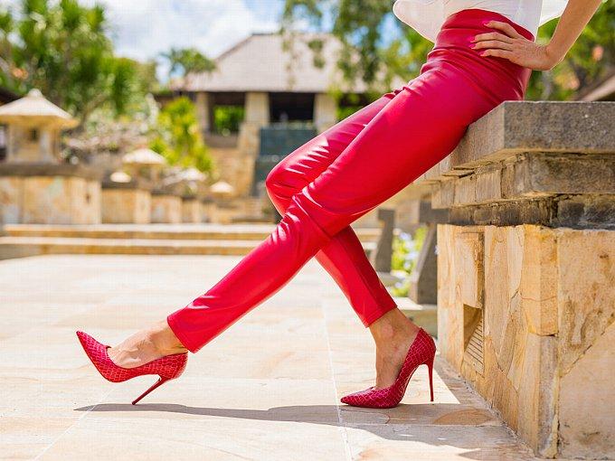 ピンクのパンツとヒールをはいた女性の足元