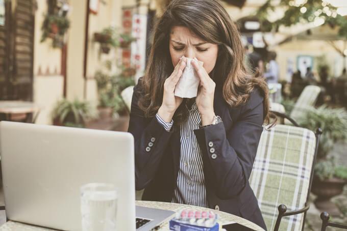 鼻をかんでいる女性の画像