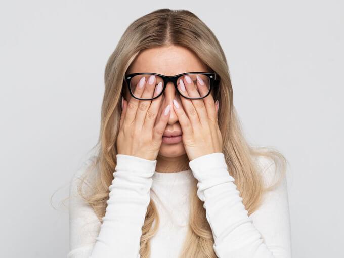 目の疲れを訴える女性の画像