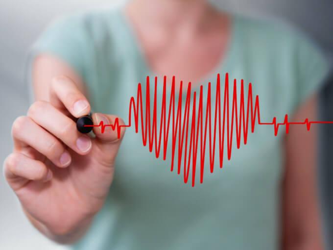 心臓の鼓動を描いている女性の画像