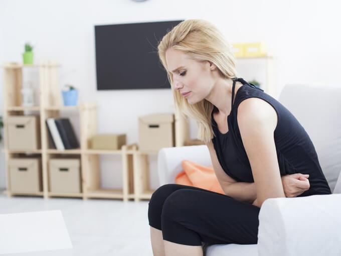 お腹を抑える女性の画像