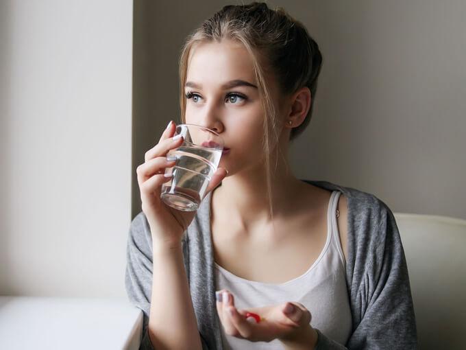 薬を飲む女性の画像
