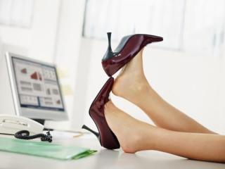 脚がむくんでだるくて机の上に投げ出している女性