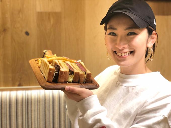 ステーキサンドを手に笑顔のヤハラさん