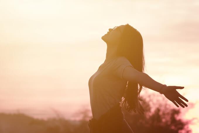 空に向かって腕を広げている女性