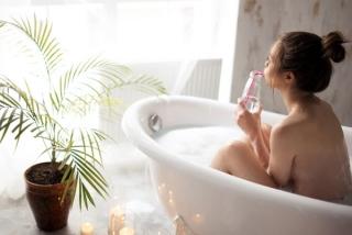 半身浴中に水を飲んでいる女性の後ろ姿の画像