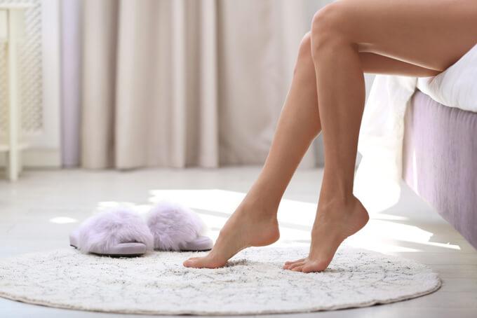 ベッドから床に足を下す女性