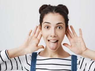 手を耳に当てながら舌を出している女性の画像
