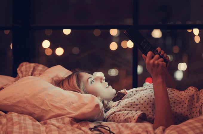 あお向けに寝ながらipadを見ている女性