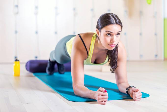床でトレーニングをする女性の画像