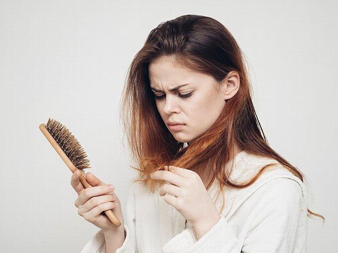 自分の髪の毛を見て不機嫌そうな女性