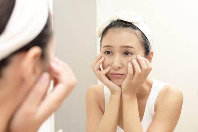 鏡を見ながら浮かない顔をしている女性の画像