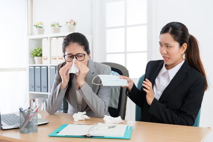 鼻水をかむ女性にマスクを渡している画像